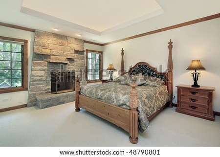 Master bedroom in luxury home with stone fireplace - stock photo