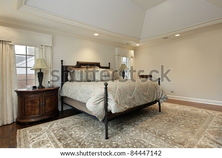 Master bedroom in luxury home with tray ceiling - stock photo