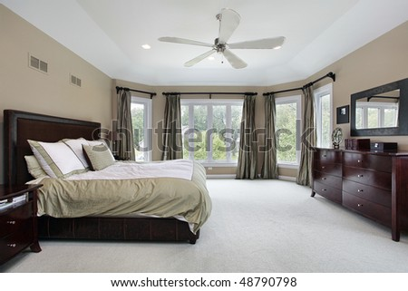 Master bedroom in luxury home with wall of windows - stock photo