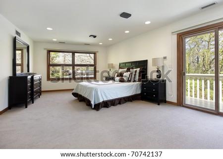 Master bedroom in luxury room with door to balcony - stock photo