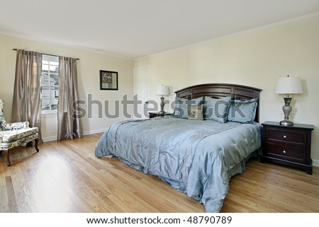 Master bedroom in remodeled home with wood flooring - stock photo