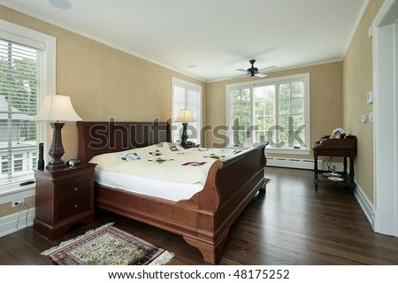 Master bedroom in suburban home with back yard view