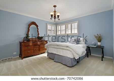 Master bedroom in suburban home with light blue walls - stock photo