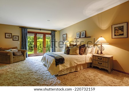 Master bedroom interior with exit to backyard.  Soft rug and queen bed with pillows create comfort interior - stock photo
