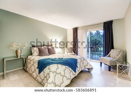 Master Bedroom Showcases Pale Green Accent Wall, Queen Size Bed Topped With  Brown Pillows,