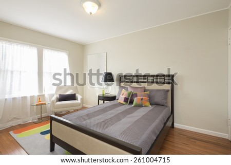 Master bedroom with armchair, pillows and night stand in modern luxury home. - stock photo