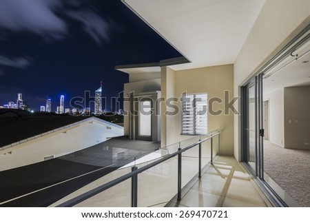 Master bedroom with balcony overlooking city skyline at night over Surfers Paradise Gold Coast Queensland Australia - stock photo