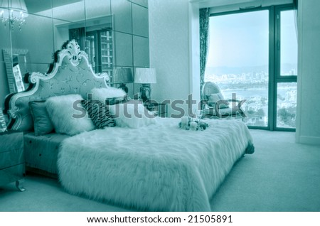 Master bedroom with beautiful bed and linens and big window - stock photo