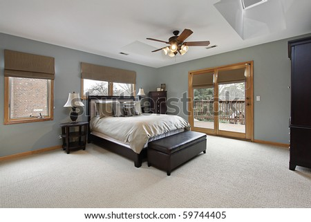 Master bedroom with doors leading to deck - stock photo