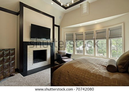 Master bedroom with fireplace and wall of windows - stock photo