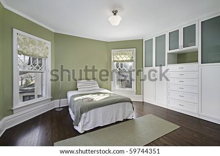 Master bedroom with green walls and dark wood flooring - stock photo