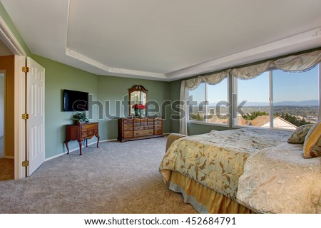 Master bedroom with green walls, vanity cabinet with mirror and floral bedding. - stock photo
