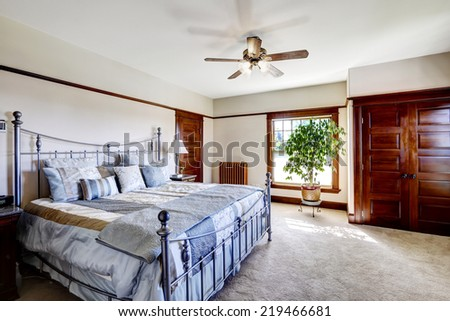 Master bedroom with iron frame bed and green tree in the corner - stock photo