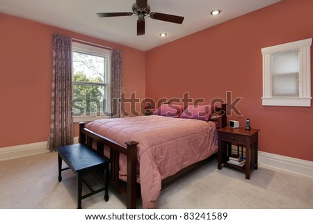 Master bedroom with peach colored walls and ceiling fan - stock photo