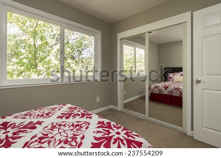 Master Bedroom with red cover. Queen sized bed with mirror. - stock photo
