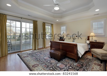 Master bedroom with tray ceiling and deck view - stock photo