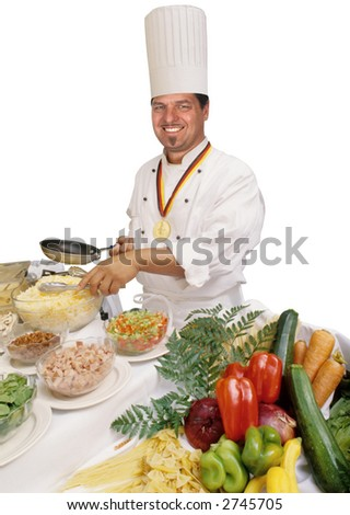 Master chef wearing culinary medal, holding pan while standing in front of a host of ingredients - stock photo