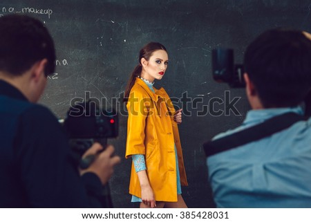 Master class for photographers. Model posing on a dark background. - stock photo
