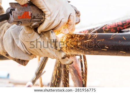 Master cleans joints angle grinder after welding - stock photo