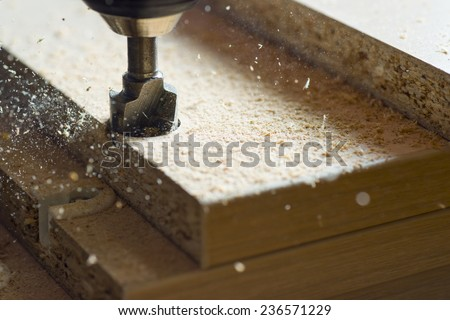 Master drill holes with a screwdriver cutter in a wooden board - stock photo