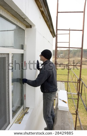 master glue winterizing the plate on wall of the building. check to accuracy of the installation