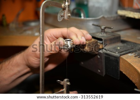 Master jeweler makes a ring of silver - stock photo