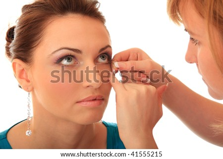 Master of style glues artificial cilia to the beautiful girl. - stock photo