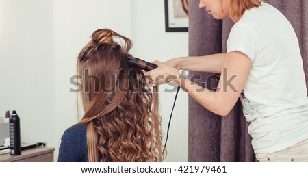 Master of style makes beautiful woman brown hair waved. - stock photo