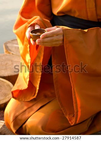 master of tea ceremony holding a cup with tea in hands - stock photo