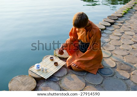 master of tea ceremony pouring tea near a lake