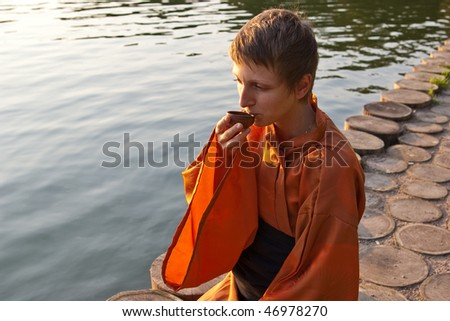 master of tea ceremony with cup in hands near the water