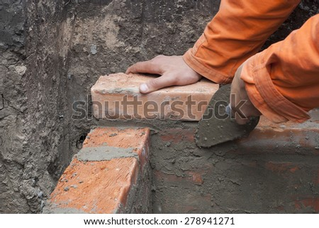 master puts a brick in cement mortar