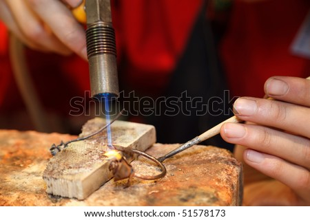 Master soldering jeweller ornament. Picture of hands and product close up. - stock photo