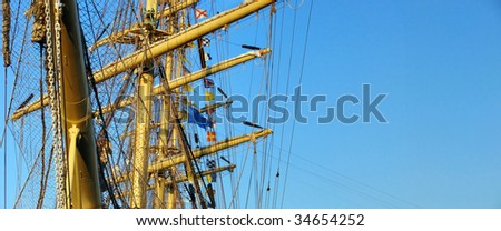 masts and details of sailing ship and blue sky - stock photo