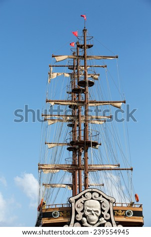 Masts and sails of huge sailing boat against the background of blue sky   - stock photo