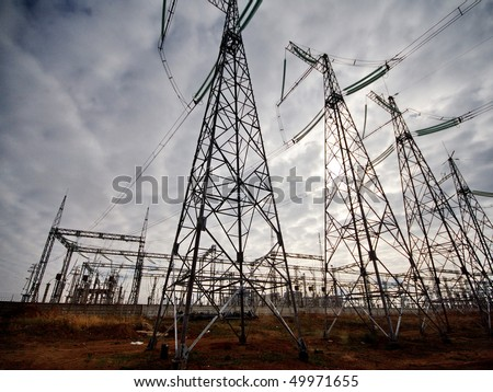 Masts of electric mains on an nuclear power station on cloudy sky background