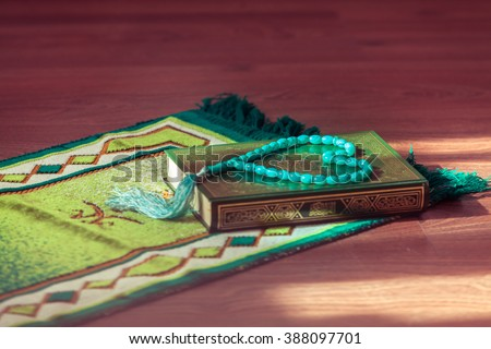 Mat for prayer , the rosary and the holy book the Koran. - stock photo