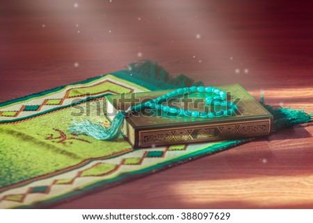 Mat for prayer , the rosary and the holy book the Koran. On the cover of the book in Arabic is written the name of the book (translated ) - Quran . - stock photo