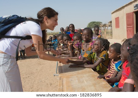MATAM,SENEGAL-CIRCA NOVEMBER 2013:Actress Caterina Murino greets the children of an elementary school,Caterina Murino is the testimonial of the NGO AMREF,circa November 2013.  - stock photo