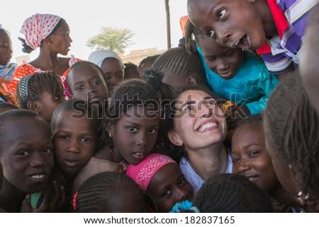 MATAM,SENEGAL-CIRCA NOVEMBER 2013:Actress Caterina Murino greets the children of an elementary school,Caterina Murino is the testimonial of the NGO AMREF,circa November 2013.  - stock photo