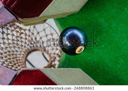 Match ball. Black eight ball in the pocket - stock photo