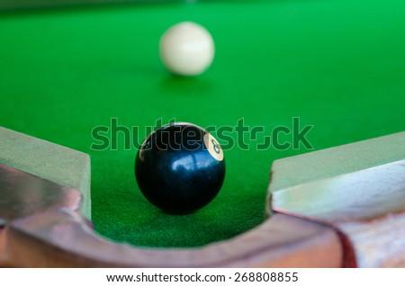 Match ball. Black eight ball to the pocket - stock photo
