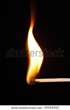 Match bursting into flame against a black background