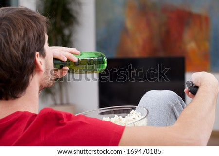 Match time, man sitting on a couch with beer and popcorn - stock photo