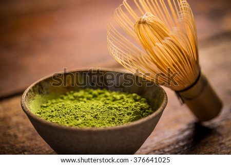 Matcha fine powdered green tea with bamboo whisk - stock photo