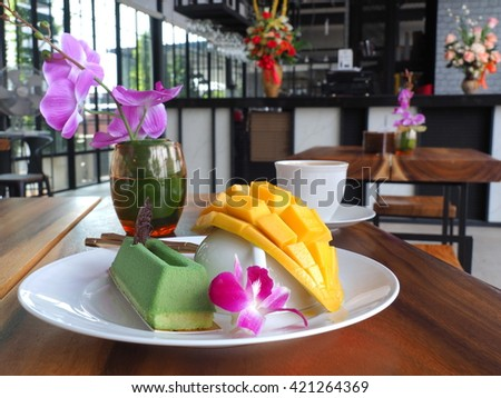 matcha green tea mousse cake with yellow ripe mango on the white dish and white coffee cup in restaurant. - stock photo