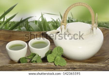 matcha green tea pot on old wooden tablet - stock photo