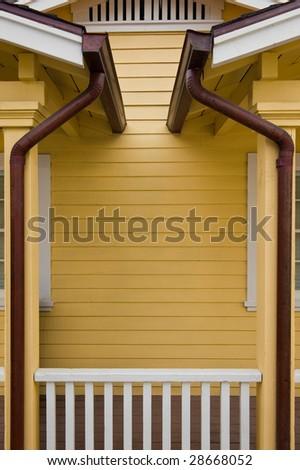 Matched copper rain gutters on the porches of a duplex - stock photo