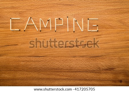 "Matches on wooden table. Matches form the word ""CAMPING"""