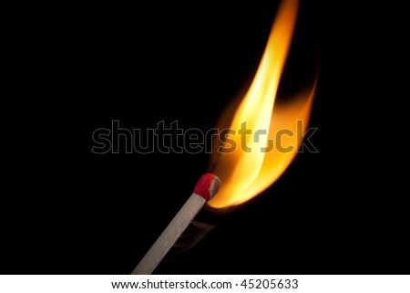 Matchstick and flame against black background - stock photo